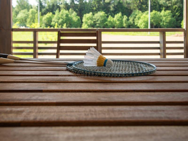 两羽毛球拍和shuttlecock在乡间别墅的大阳台的一张木桌上说谎 在的豪华的绿色叶子 库存照片