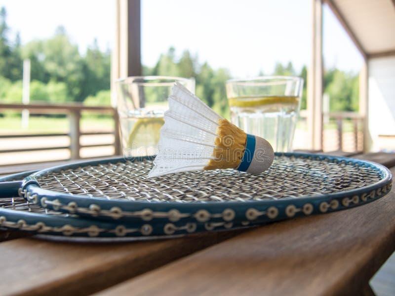 两羽毛球拍和shuttlecock在前景在一张木桌上 两块玻璃用与切片的刷新的柠檬水  库存图片