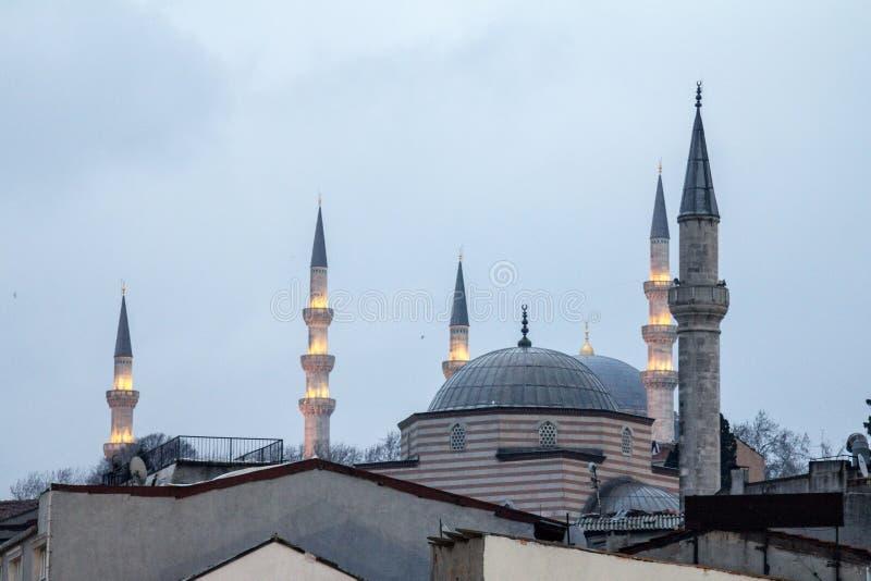 两老无背长椅样式清真寺、法提赫和Ismet Efendi Tekke Camii尖塔和圆顶,被采取在黄昏 图库摄影