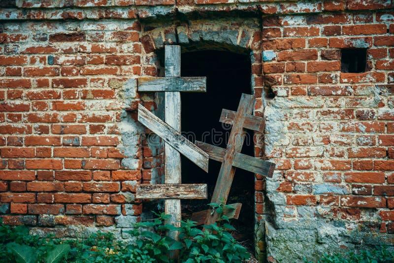 两老木发怒块对砖古老古色古香的坟茔的入口在被放弃的公墓 免版税图库摄影