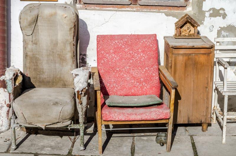 两老葡萄酒减速火箭打破的斜倚供以座位在白色有镇压和老床边的被粉刷的墙壁背景的porvanoy布料  免版税库存图片