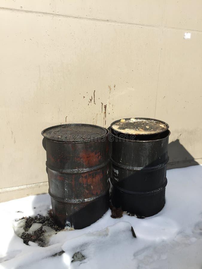 两肮脏的油腻桶特写镜头在大厦之外的在雪 库存照片
