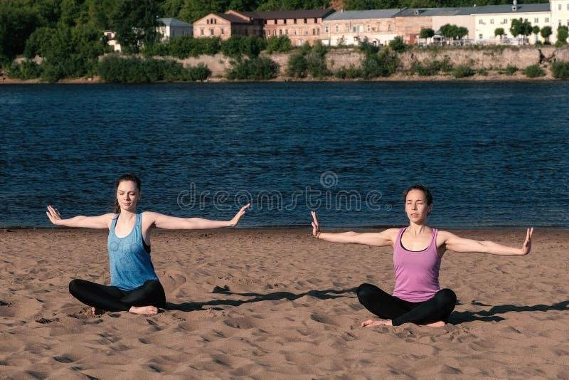 两舒展在海滩的妇女瑜伽由河在城市 美好的城市视图 实施对边 免版税图库摄影