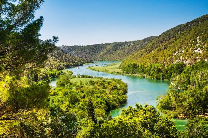 两艘船在河航行 在森林和山附近 克尔卡河,国立公园,达尔马提亚,克罗地亚 免版税库存图片