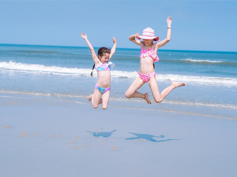 两获得在热带海滩的乐趣和跳跃在泳装的年轻愉快的女孩入在沿海的空气在白天 图库摄影