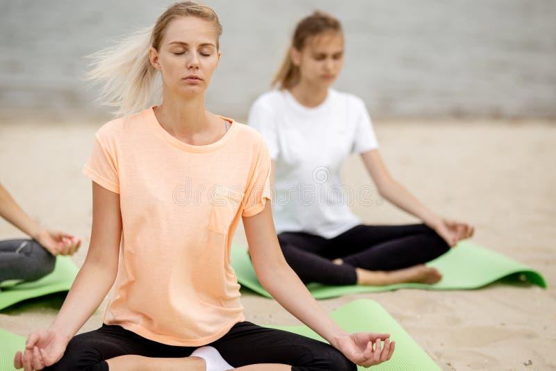 两轻松的少女在与做瑜伽的结束眼睛的莲花坐坐在席子在沙滩在一温暖的天 免版税库存图片