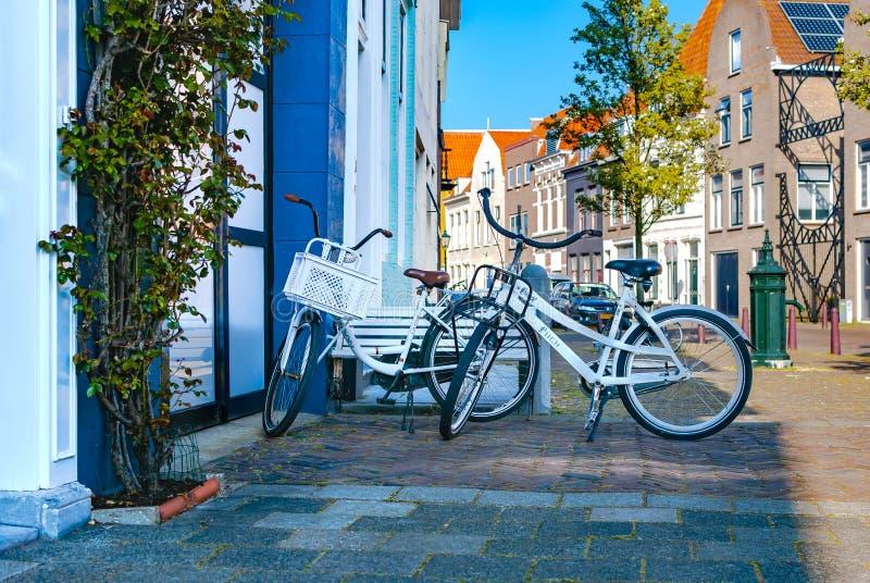 两辆白色浪漫自行车站立在彼此附近和停放在街道附近 室外的活动 背景概念框架沙子贝壳夏天 库存图片