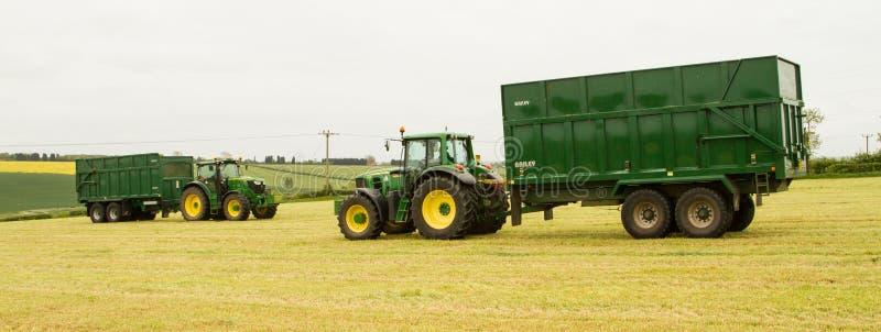 两辆绿色拖拉机的和贝里拖车的 库存图片