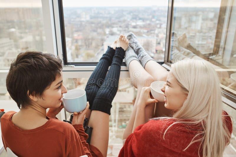 两逗人喜爱和坐阳台,饮用的咖啡和聊天与在窗口倾斜的被舒展的腿的愉快的妇女 库存图片