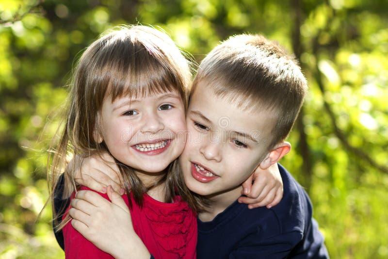 两逗人喜爱的白肤金发的滑稽的愉快的微笑的儿童兄弟姐妹,接受姐妹明亮的晴朗的绿色bokeh的年轻男孩兄弟女孩户外 免版税图库摄影