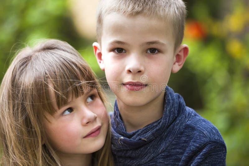 两逗人喜爱的金发儿童兄弟姐妹、年轻男孩兄弟和姐妹女孩户外明亮的晴朗的绿色bokeh背景的 ?? 库存图片