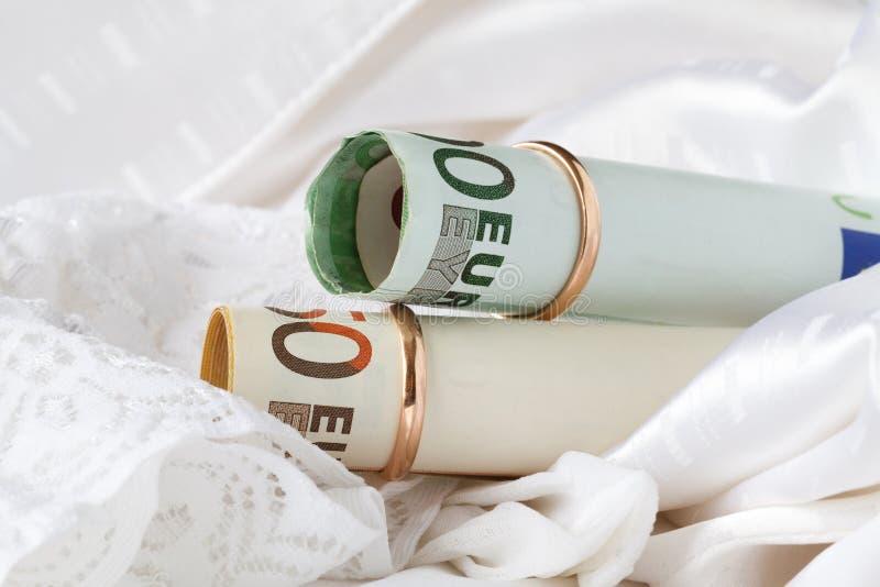 两金子婚戒在钞票欧元穿戴了 库存图片