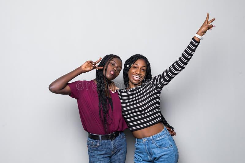 两非洲妇女做面孔在白色背景隔绝的照相机 免版税库存图片
