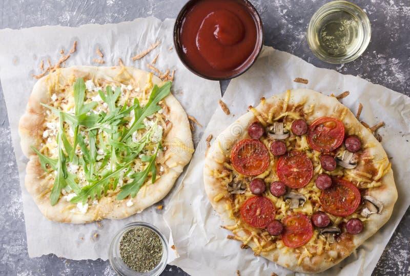 两顶视图比萨:素食主义者和比萨用肉、碗有油的,调味汁和干草本 库存照片