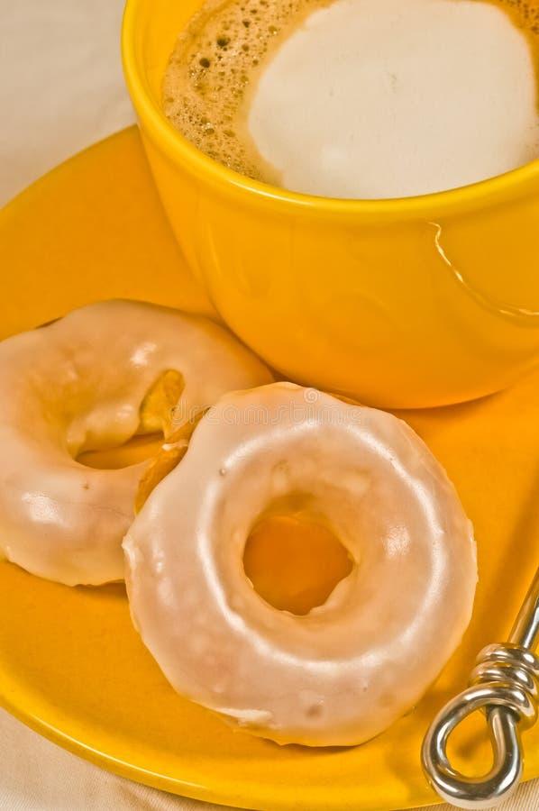 两,新近地烘烤,自创,与香草结霜的奶油蛋卷油炸圈饼,在有一个黄色杯子的一块黄色板材热的cappucino 库存图片