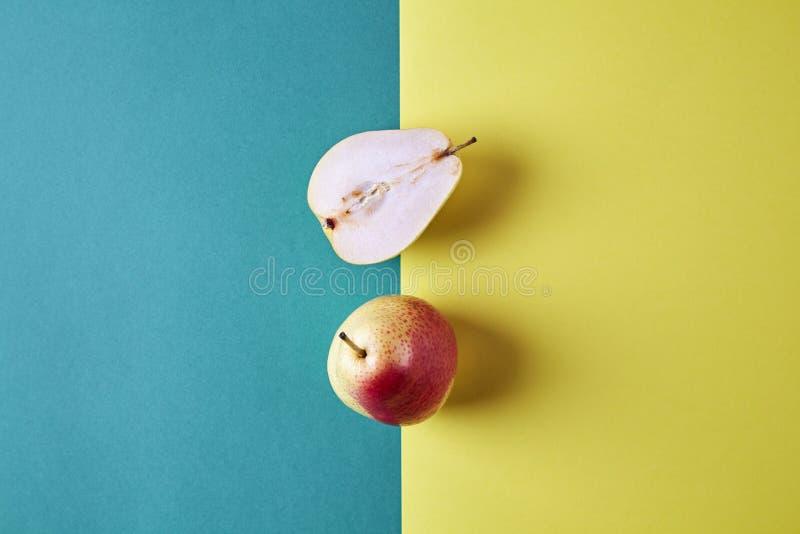 两整个新鲜的梨,果子从上面切成了两半看法在绿色黄色背景,现代样式食物图片,样式设计 免版税图库摄影
