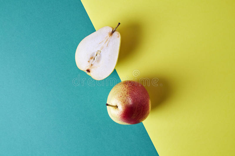 两整个新鲜的梨,果子从上面切成了两半看法在绿色黄色背景,现代样式食物图片,样式设计 免版税库存照片
