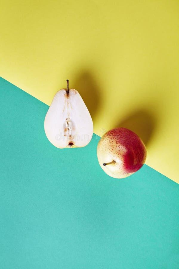 两整个新鲜的梨,果子从上面切成了两半看法在绿色黄色背景,现代样式食物图片,样式设计 图库摄影