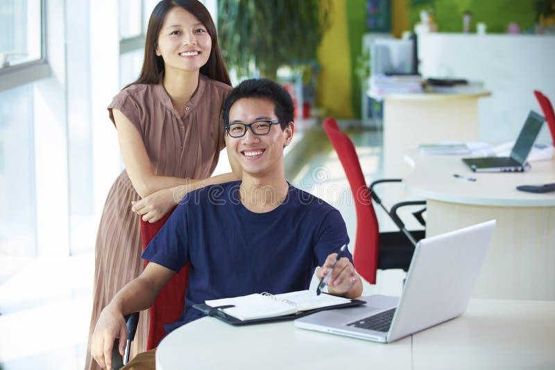 两年轻亚裔买卖人在办公室 库存照片