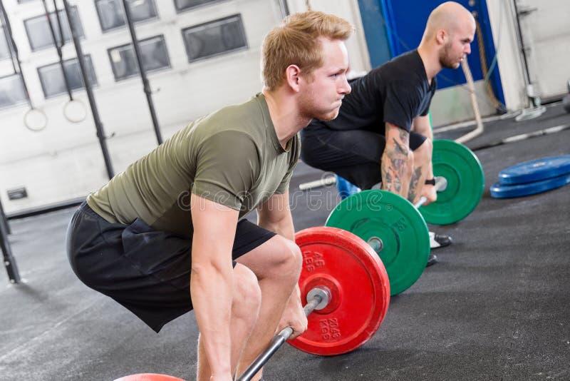 两致力了人火车deadlift在健身健身房中心 图库摄影