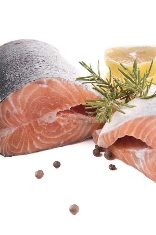 两件新鲜的三文鱼用柠檬和迷迭香在白色bac 免版税库存图片