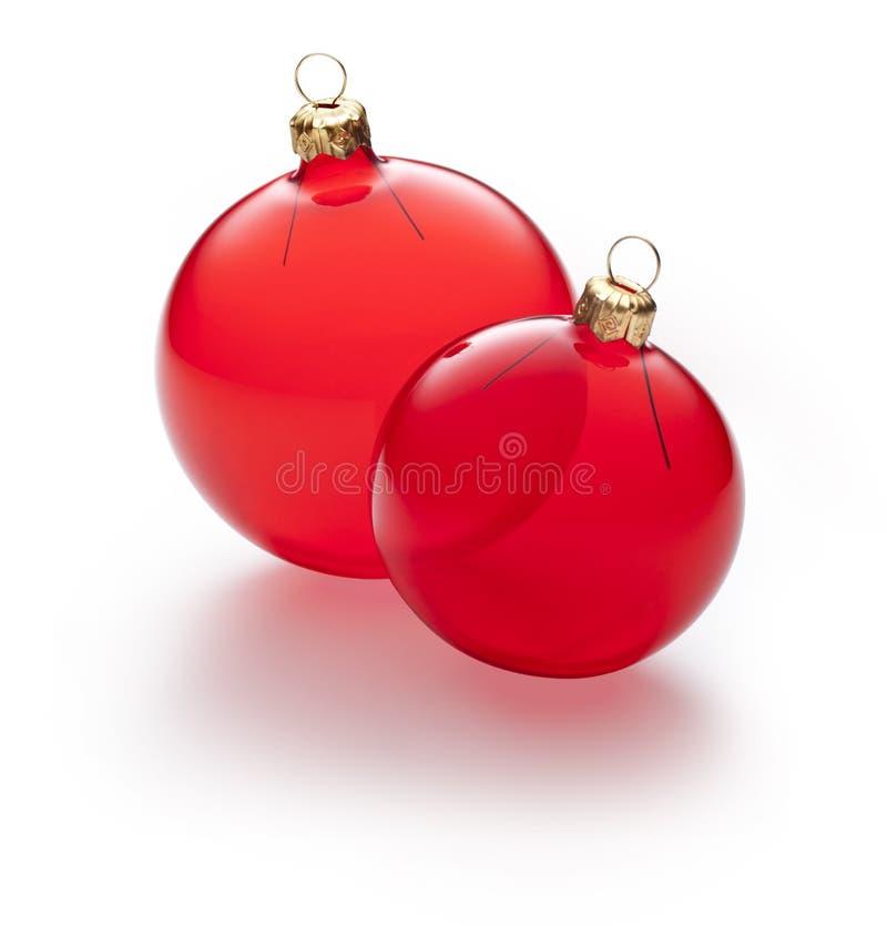 两件清楚的红色圣诞节装饰品 库存照片