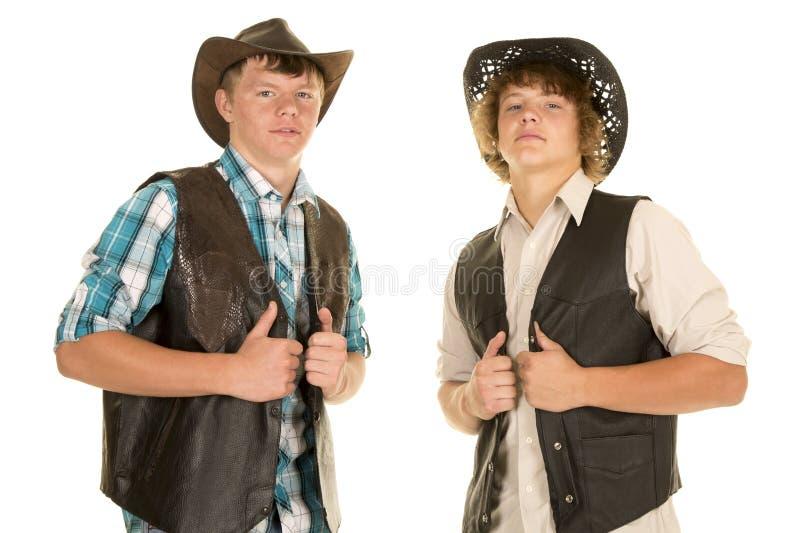 两件年轻牛仔举行背心 图库摄影