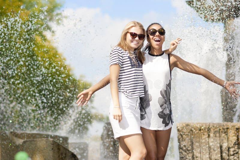 两滑稽和一起拥抱笑的少年的女朋友 摆在反对喷泉在公园户外 免版税库存图片