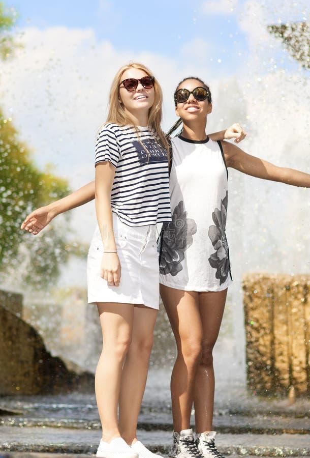 两滑稽和一起拥抱笑的少年的女朋友 摆在反对喷泉在公园户外 免版税库存照片