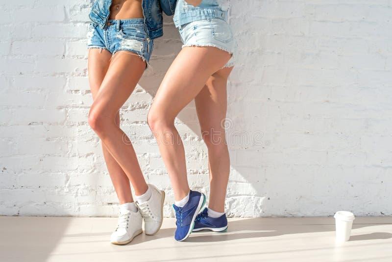 两件美丽的妇女牛仔裤的运动的长的性感的腿 库存图片