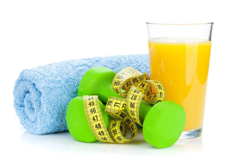 两绿色dumbells、卷尺和橙汁 健身和h 免版税库存图片
