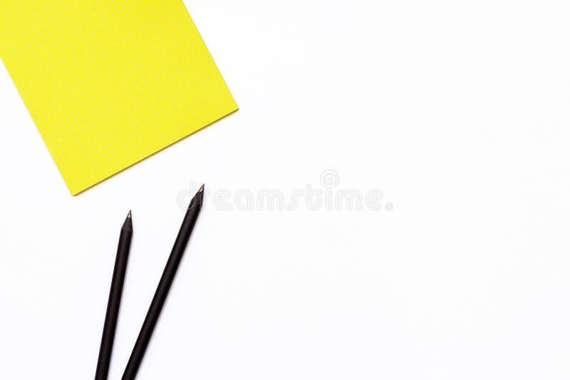 两黑铅笔和一个黄色笔记薄在白色背景 工作地点的最小的企业概念在办公室 免版税库存照片