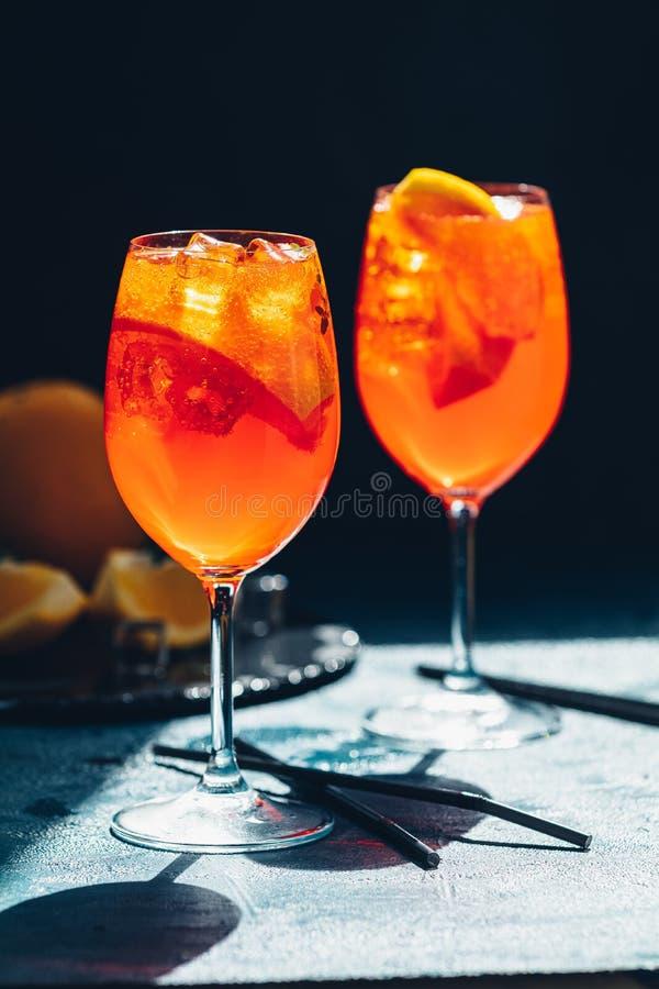 两Aperol喷在大酒杯用桔子,夏天意大利新鲜的酒精冷的饮料的鸡尾酒 黑暗的酒吧柜台背景 库存照片