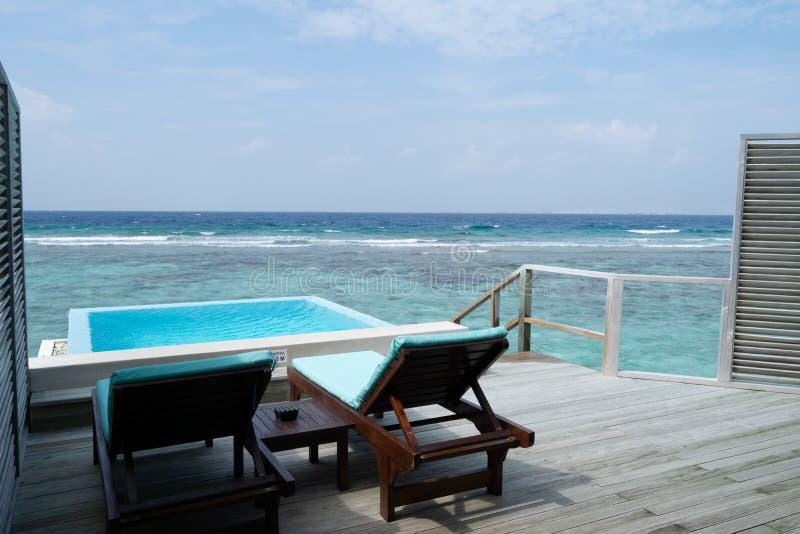 两deckchair和一个水池在大阳台在美丽的平房 库存图片