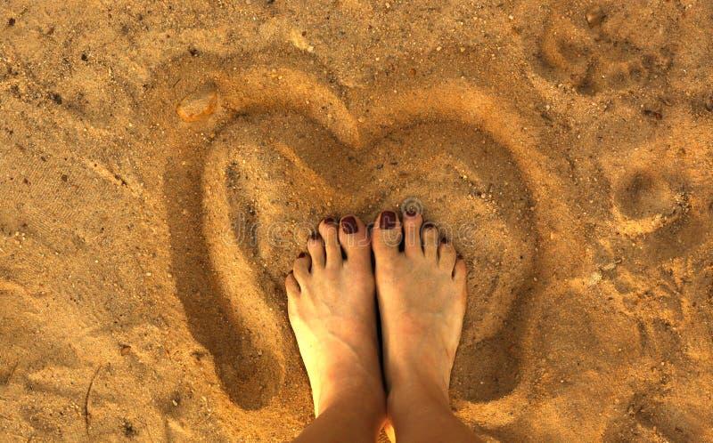 两femile pedicured英尺,在沙子心脏里面的沙子 免版税图库摄影