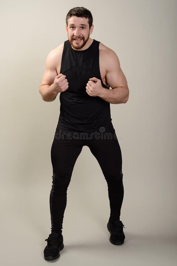严厉有胡子中间agedfighter在一个前面防护姿势反对灰色背景 免版税图库摄影