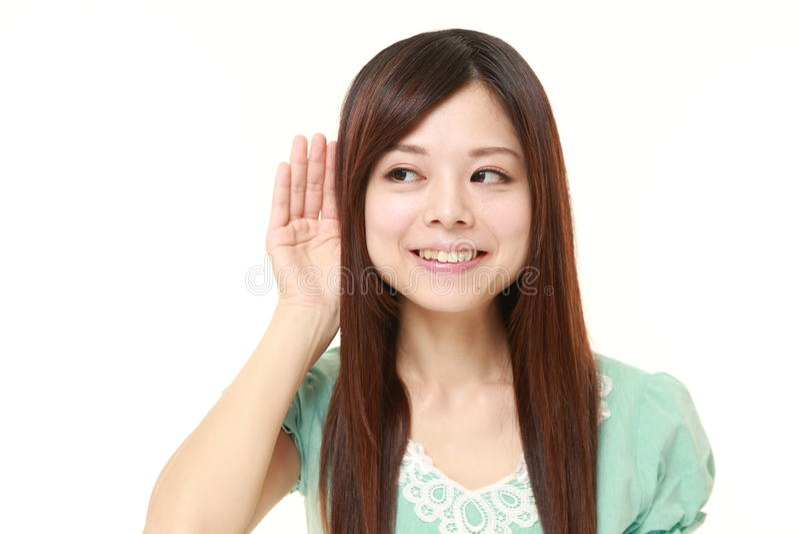 严密地听的少妇用在耳朵后的手 库存照片