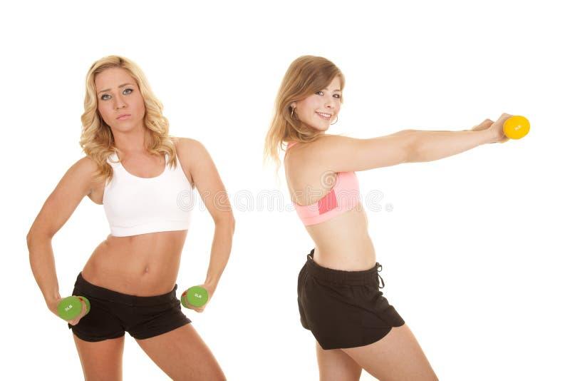 严肃两女孩体育胸罩的重量 库存照片