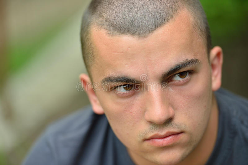 严肃和哀伤的英俊的年轻人画象户外在natur 图库摄影