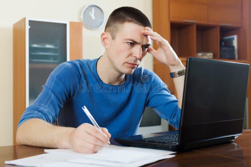 严肃在膝上型计算机的人凝视财政文件 免版税库存照片