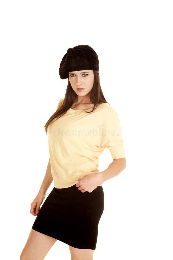 严肃妇女黄色衬衣黑帽会议立场的边 图库摄影