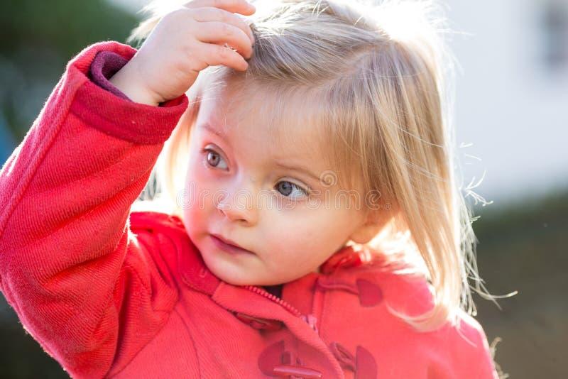 严肃室外想法或哀伤的年轻婴孩白种人白肤金发的真正的人女孩关闭的画象 库存照片