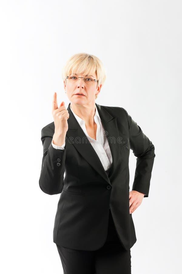 严肃成熟女实业家打手势 免版税库存照片