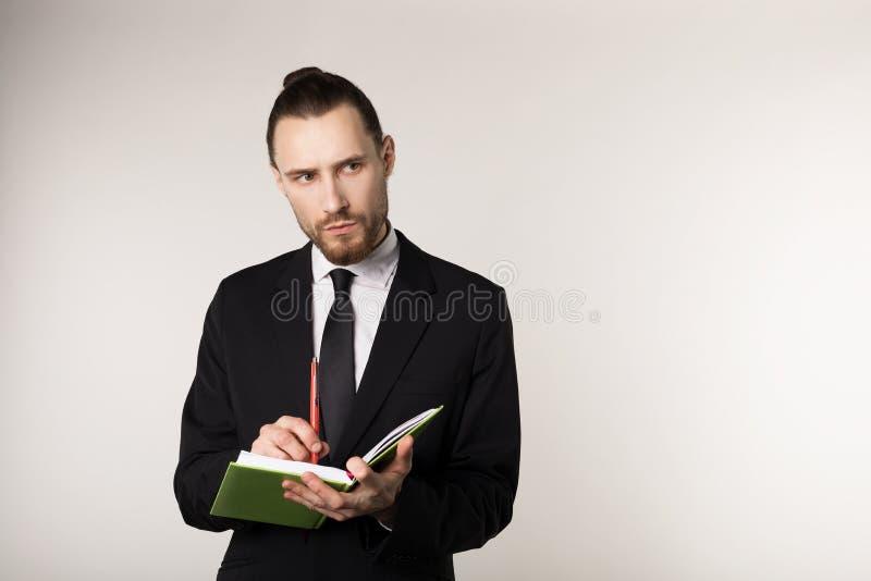 严肃的不剃须的商人射击的腰部在殷勤地听他的商务伙伴和作为的黑衣服的 图库摄影