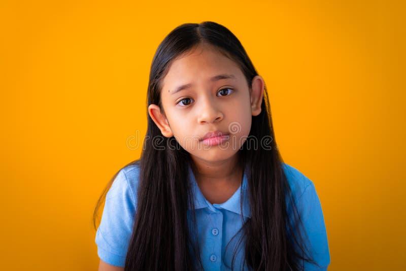 严肃的亚裔逗人喜爱的女孩橙色背景画象  库存照片