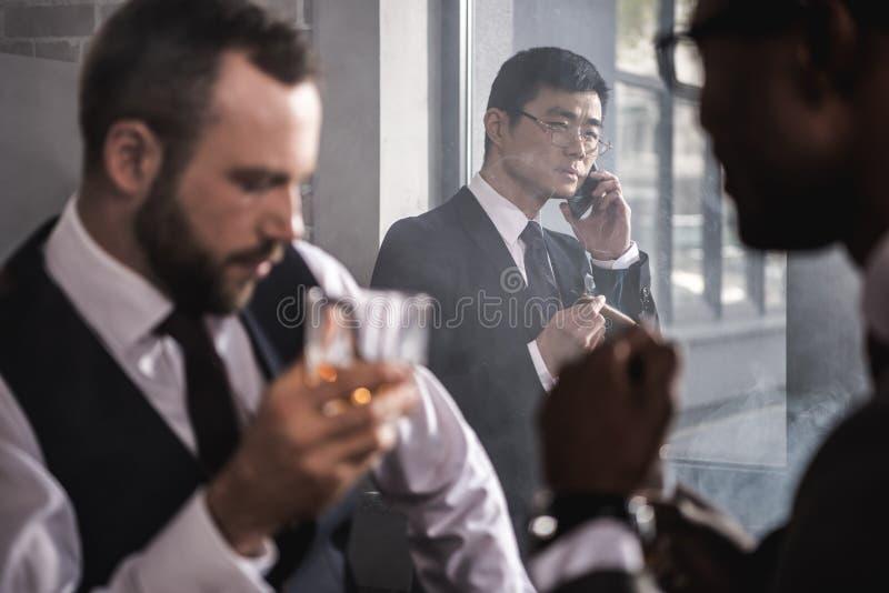 严肃的亚洲商人抽烟的雪茄和谈话在智能手机,当喝威士忌酒时的同事 免版税库存照片
