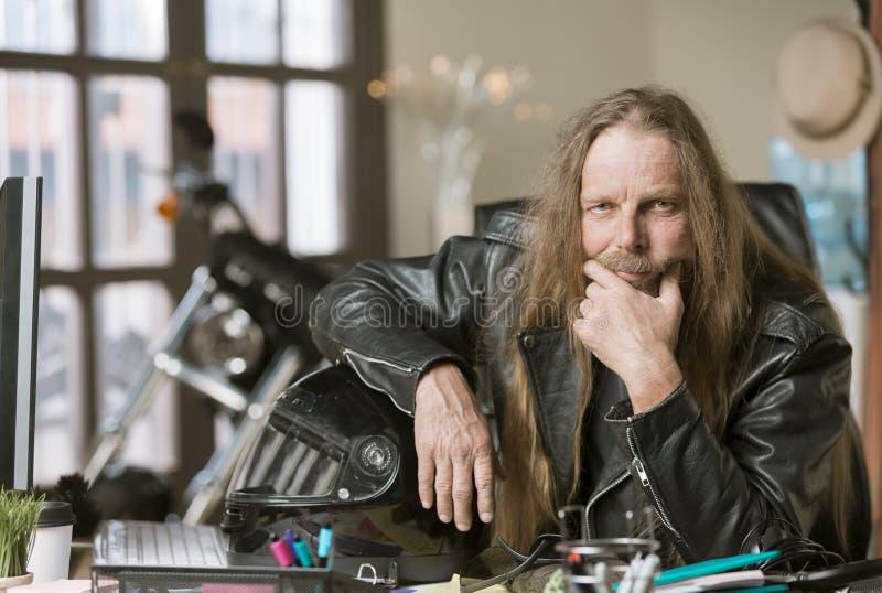 严肃的人在他的有摩托车和盔甲的办公室 免版税库存图片