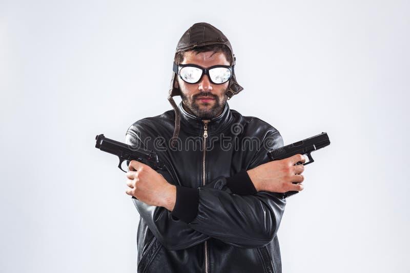 严肃的人在他的手上的拿着两杆枪 免版税库存图片