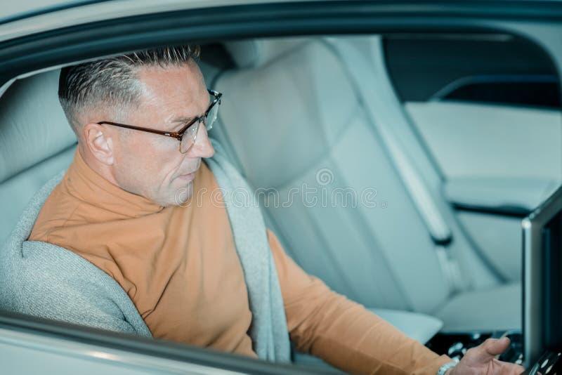 严肃的人坐汽车的后座 免版税图库摄影