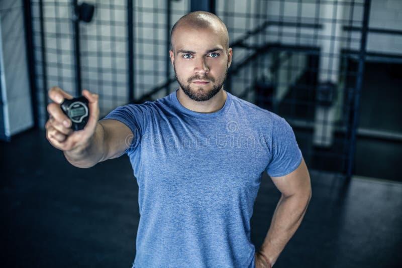 严肃的体育教练的画象有一个秃头的 在健身房的照相机显示一块秒表 锻炼是成功的 ??  免版税库存照片